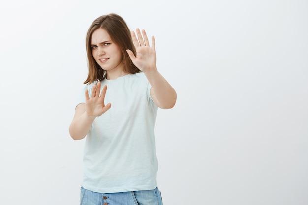Enlevez-moi ça. portrait de femme européenne mignonne mécontent et irrité intense en t-shirt à la mode couvrant le visage avec les bras tirés se détournant avec un regard mécontent d'être aveuglé par une lampe de poche