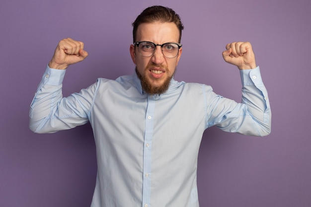 Ennuyé bel homme blond dans des lunettes optiques garde les poings isolés sur le mur violet
