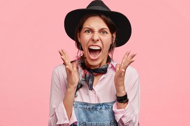 Ennuyé belle femme agricultrice en chapeau et salopette en jean, fait des gestes avec colère et garde la bouche largement ouverte, a une expression désespérée, isolée sur un mur rose