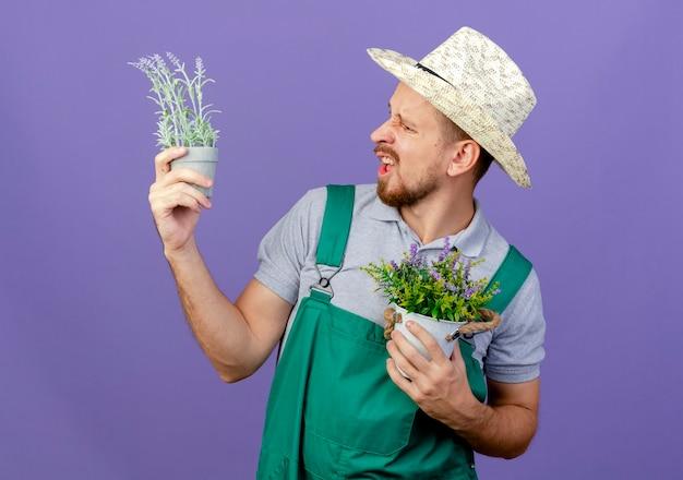 Ennuyé jeune beau jardinier slave en uniforme et chapeau tenant et regardant des pots de fleurs isolés sur un mur violet avec copie espace
