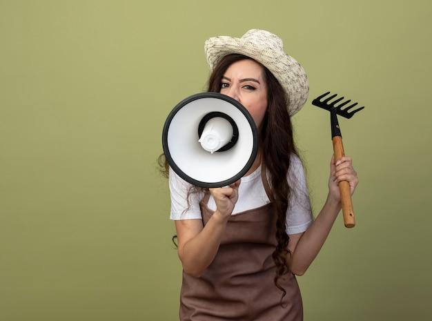 Ennuyé jeune femme jardinière en uniforme portant chapeau de jardinage détient râteau et crie en haut-parleur isolé sur mur vert olive