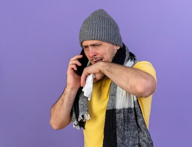 Ennuyé jeune homme slave malade blonde portant un chapeau d'hiver et une écharpe détient des tissus parlant au téléphone