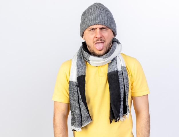 Ennuyé jeune homme slave malade blonde portant un chapeau d'hiver et une écharpe sort la langue isolé sur un mur blanc avec copie espace