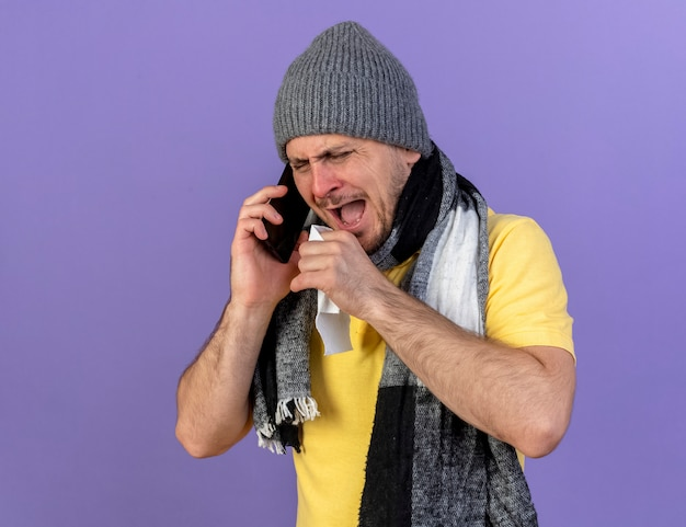Ennuyé jeune homme slave malade blonde portant un chapeau d'hiver et une écharpe tient des discussions sur les tissus au téléphone