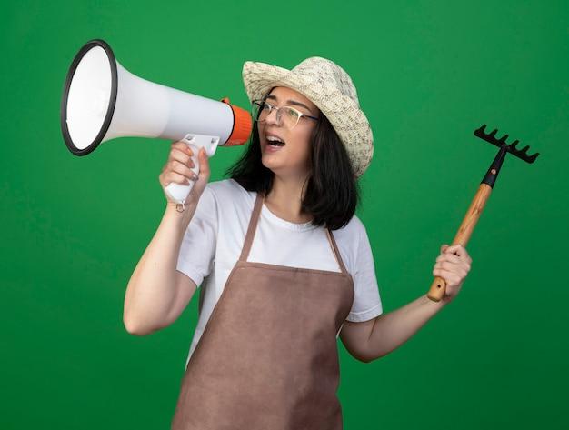 Ennuyé jeune jardinière brune à lunettes optiques et uniforme portant un chapeau de jardinage tient le râteau et crie dans le haut-parleur à côté isolé sur mur vert