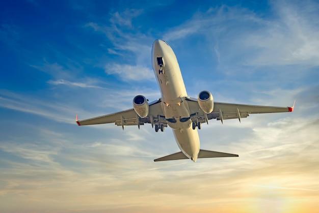 Un énorme avion tourné en vol contre le ciel coucher de soleil du soir
