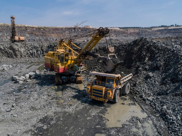 Énorme camion-benne industriel chargé par une excavatrice dans une carrière de pierre chargée transportant du marbre ou du granit tiré d'un drone