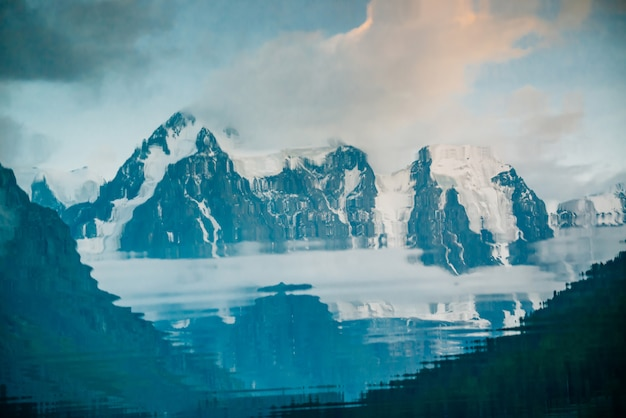 Énorme glacier reflété dans la surface de l'eau. réflexion de l'eau des montagnes rocheuses enneigées géantes sous le ciel nuageux. épais brouillard en montagne. paysage atmosphérique. reflet tranquille dans le lac de montagne.