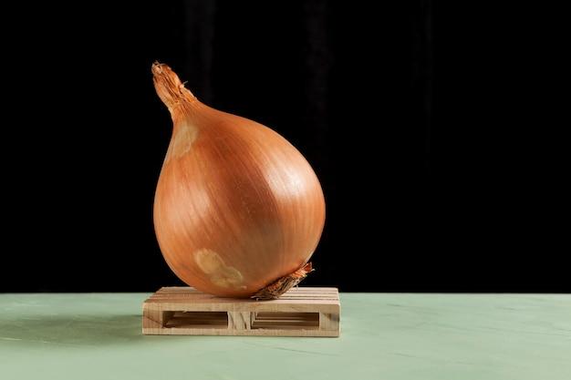 Un énorme oignon laid se trouve sur une palette en bois.