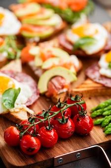 Énorme petit-déjeuner sain avec des tomates séchées au soleil, des sandwiches avec des œufs brouillés, des saucisses, du saumon, de la roquette, du fromage blanc, de l'avocat sur une planche de bois