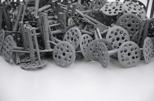 Une énorme pile de boulons en plastique avec des chapeaux ronds troués repose sur une plaque de polystyrène en mousse grise