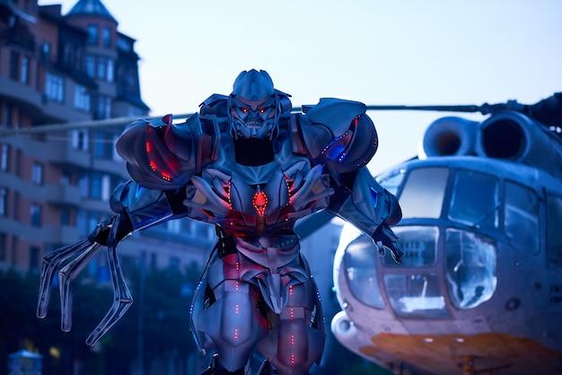 Énorme robot-transformateur se déplaçant à proximité d'un hélicoptère militaire dans le centre-ville.