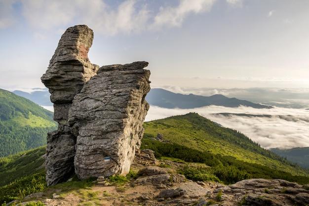 Énorme rocher rocheux calcaire sur le sommet d'une montagne verte remplie de nuages gonflés blancs et de brouillard, vue de couvert de crête de montagne de forêt à feuilles persistantes et d'espace de copie bleu clair