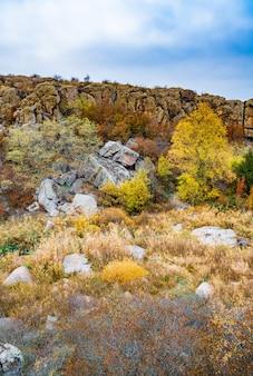 D'énormes dépôts de vieux minéraux en pierre recouverts de végétation dans une prairie remplie de soleil chaud