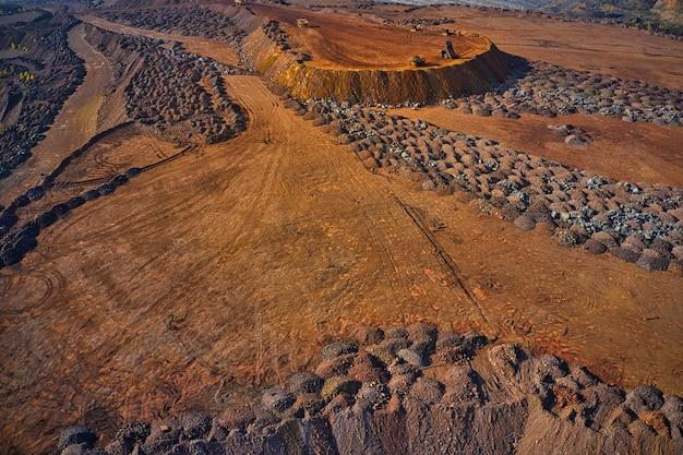 D'énormes monticules de déchets de minerai de fer près de la carrière. camions belaz conduisant dans une usine minière, carrière de mine en ukraine