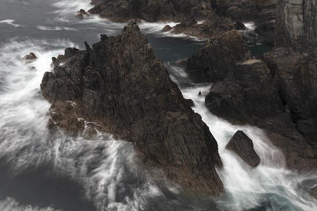 D'énormes rochers au milieu d'une mer capturés par une journée nuageuse