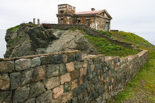 Énormes rochers sur l'océan, paysage d'été de la mer, vieux bâtiment en pierre et clôture sur une haute falaise, phare de gamova, russie, russie, primorsky krai, peter the great bay, babkin's cape.