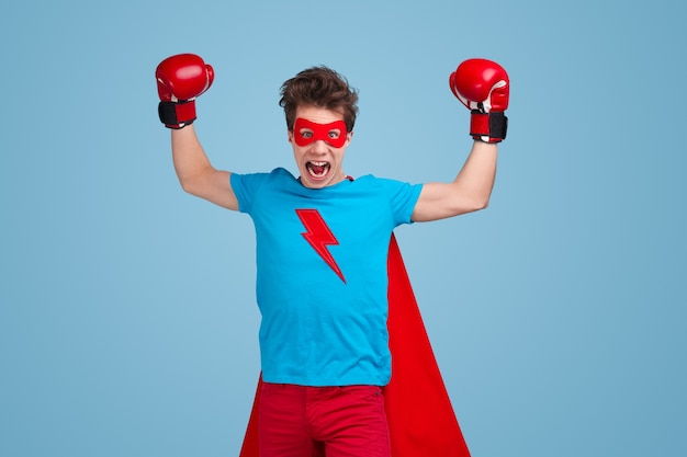 Enragé jeune mec en costume de super-héros et gants de boxe levant les bras et hurlant pendant le combat sur fond bleu