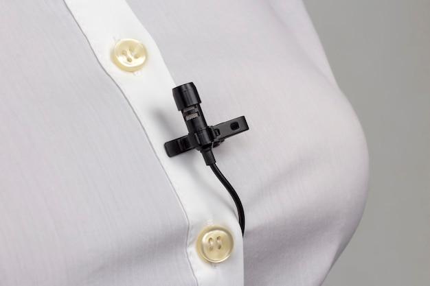 Enregistrement audio du son sur un microphone à condensateur. le microphone cravate est fixé avec un clip sur un gros plan de chemise de femme