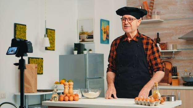 Enregistrement de boulanger pour podcast dans la cuisine tout en tamisant la farine sur la table. chef influenceur blogueur à la retraite utilisant la technologie internet pour communiquer, tirer, bloguer sur les réseaux sociaux avec un équipement numérique