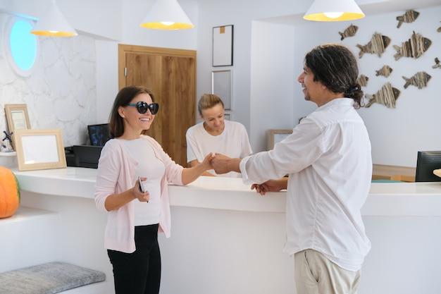 Enregistrement des clients à l'hôtel, réceptionnistes masculins et féminins debout à la réception pour parler et accueillir une femme