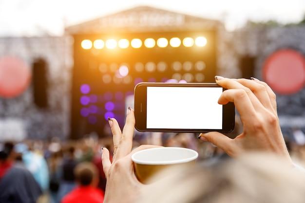 Enregistrement d'un concert de musique en plein air sur un téléphone mobile. écran blanc