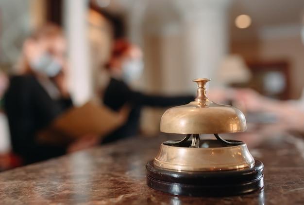 Enregistrement à l'hôtel. réceptionniste au comptoir de l'hôtel portant des masques médicaux par mesure de précaution contre le virus. jeune femme en voyage d'affaires faisant l'enregistrement à l'hôtel