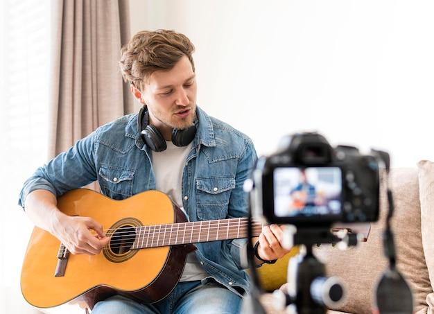 Enregistrement masculin beau tout en jouant de la guitare