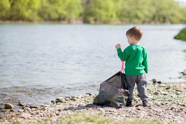 Enregistrer le concept d'environnement, un petit garçon ramassant des ordures et des bouteilles en plastique sur la plage pour les jeter à la poubelle.