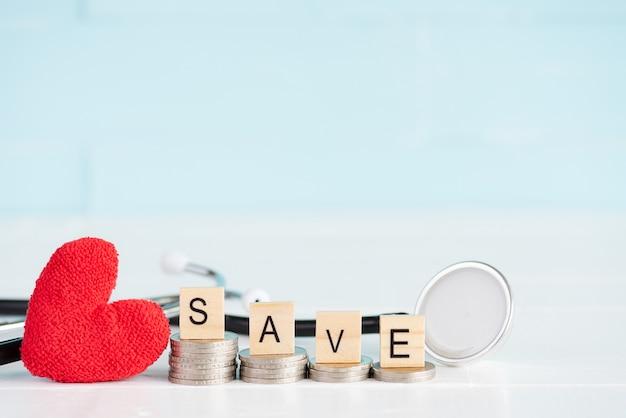 Enregistrer le texte sur la pile de pièces de monnaie avec stéthoscope et coeur rouge sur fond en bois.