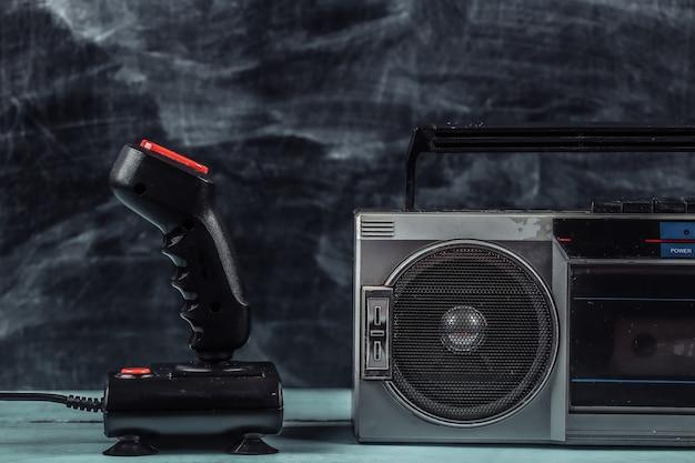 Enregistreur de cassettes radio stéréo portable rétro des années 80 et joystick sur fond de tableau noir.