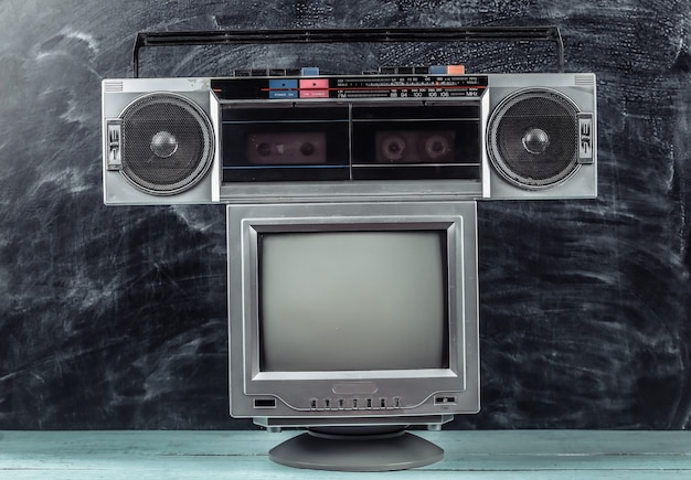 Enregistreur de cassettes radio stéréo portable rétro des années 80, téléviseur sur fond de tableau noir