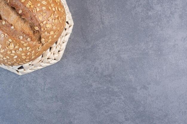 Enrobage de flocons sur une miche de pain sur un panier à l'envers sur fond de marbre. photo de haute qualité