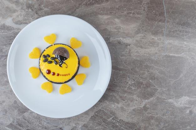 Enrobage de saveur de citron sur un petit gâteau sur un plateau sur une surface en marbre