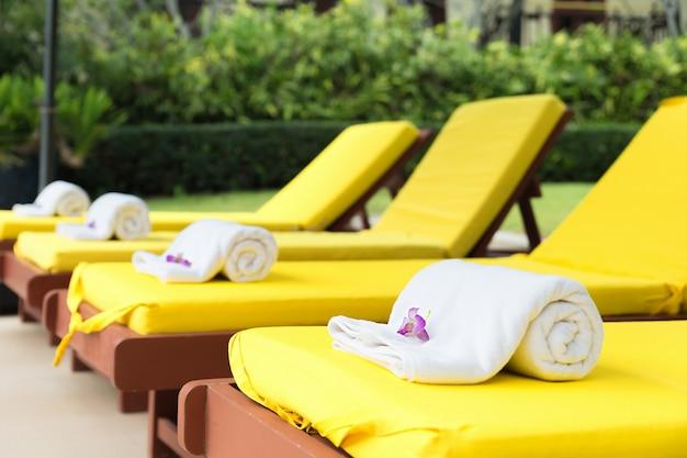 Enroulé des serviettes sur des chaises jaunes dans la piscine au resort.