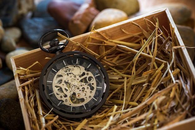 Enrouleur de montre de poche sur paille de blé naturelle dans une boîte en bois.