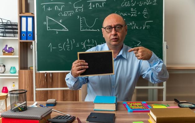 Un enseignant d'âge moyen concerné est assis à table avec des fournitures scolaires tenant et pointe vers un mini tableau noir en classe