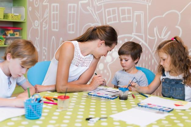 Enseignant aidant l'enfant à peindre
