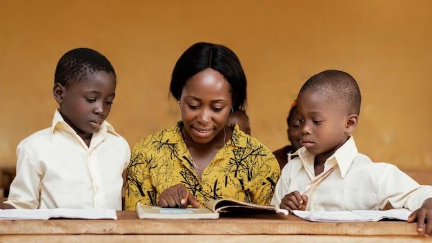 Enseignant aidant les enfants en classe