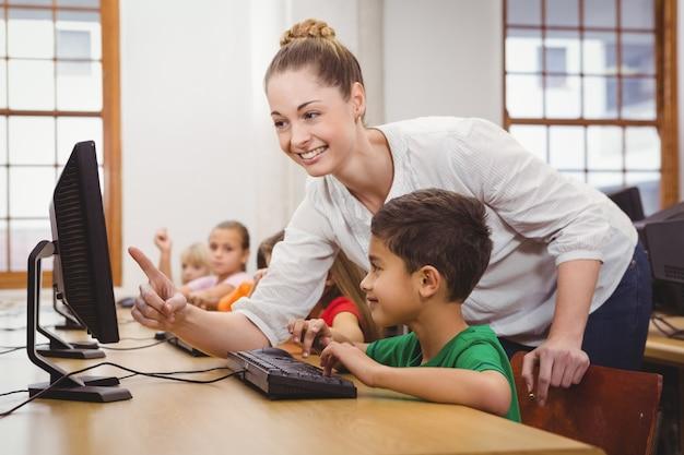 Enseignant aidant un étudiant à l'aide d'un ordinateur