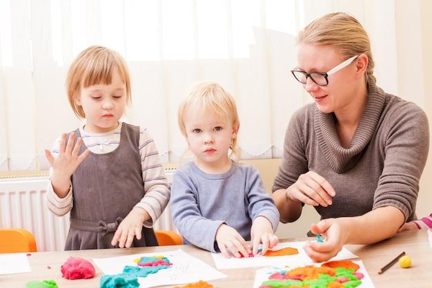 L'enseignant aide le garçon à faire une pâte à modeler sur la table