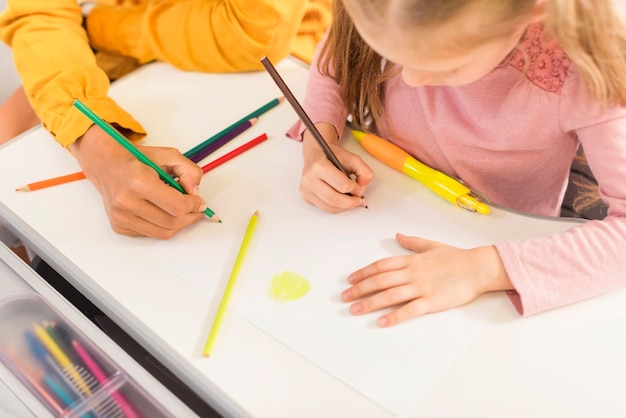 Enseignant à angle élevé aidant un élève en classe