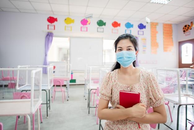 Un enseignant asiatique porte un masque dans la salle de classe et à l'école sur le point de commencer