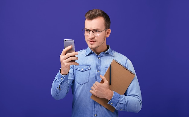 Enseignant en chemise en jean regardant attentivement sur téléphone mobile attentivement