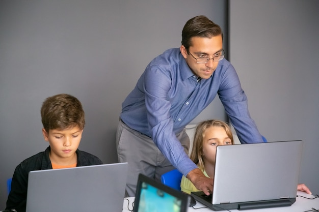 Enseignant ciblé aidant une fille avec une tâche et en tapant sur le clavier