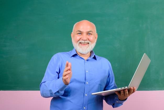 Enseignant en classe près d'un enseignant de tableau noir donnant une leçon aux élèves de l'école d'éducation