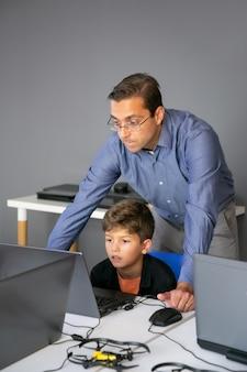 Enseignant de contenu vérifiant la tâche et debout derrière l'élève