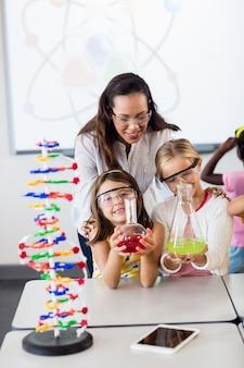 Enseignant avec deux élèves mignons faisant de la science