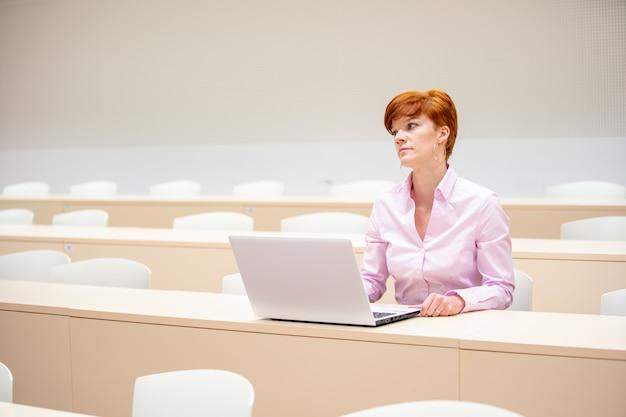 Un enseignant du secondaire écrit des devoirs pour les élèves dans son ordinateur portable blanc