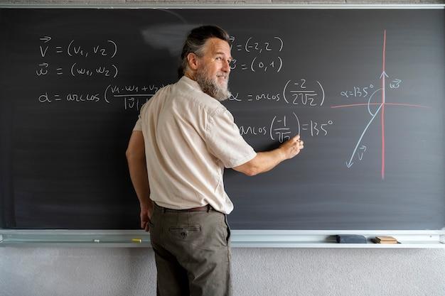 Un enseignant du secondaire écrit des formules mathématiques sur un tableau noir avec de la craie espace de copie éducation